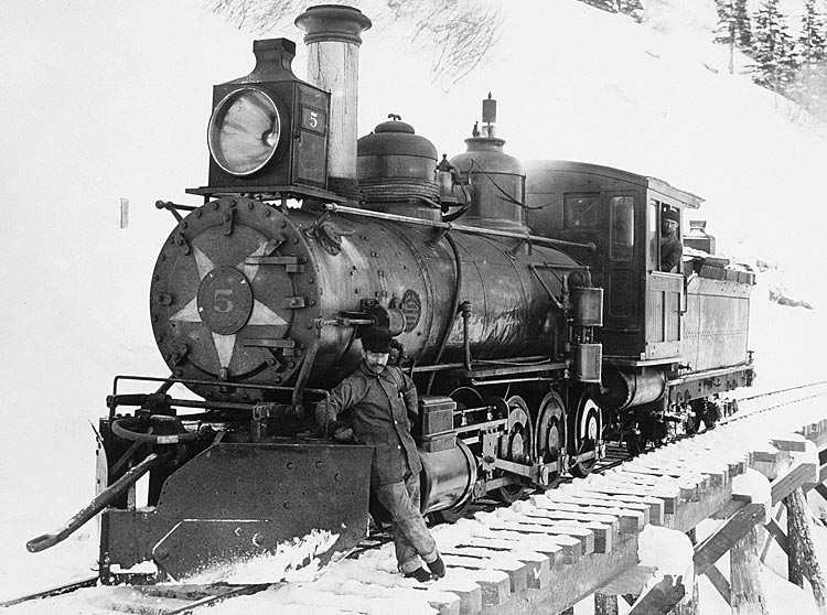 Photo: John Call Benedict, engineer, stops for a photo with Steam Engine No.5 in 1900.