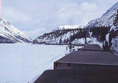 Northbound train at Guard Rail Curve, Lake Bennett. Location:MP 43. Milepost:Mile 43.6. Date:1980-03-00